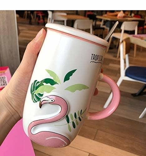 A hand holding up a flamingo mug with a lid.