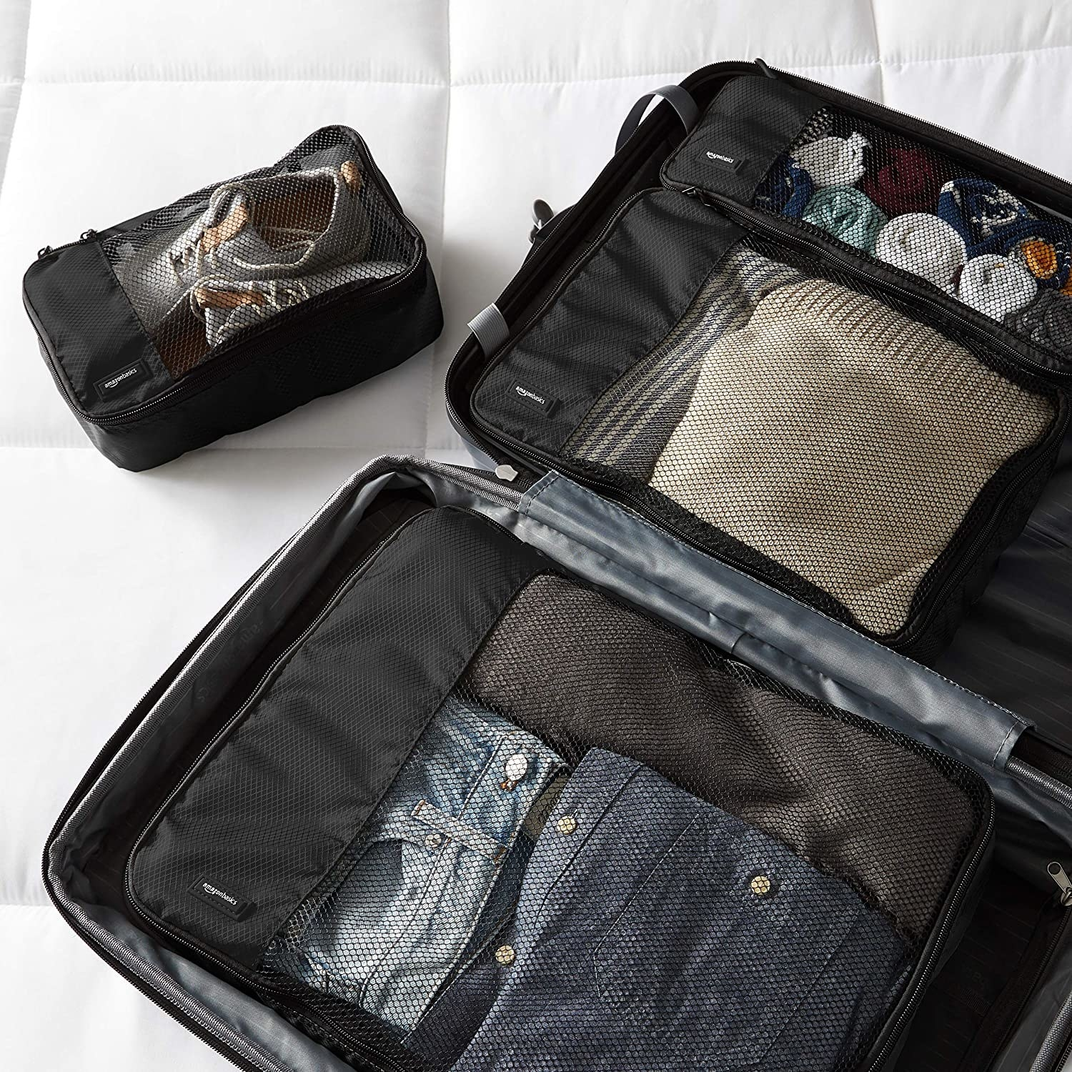 Packing cubes with clothes pictured inside a suitcase.