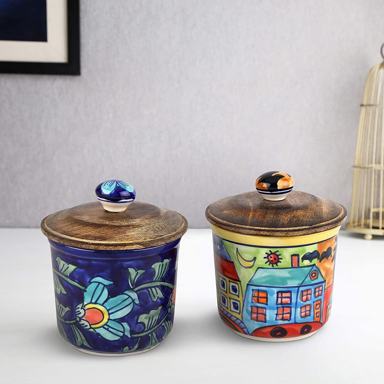 Set of 2 colourful ceramic jars with wooden lids and hand painted flowers and houses.
