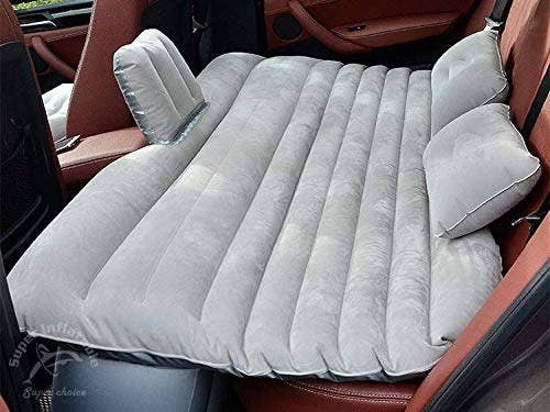 The car mattress inflated and set up in the back seat of a car.