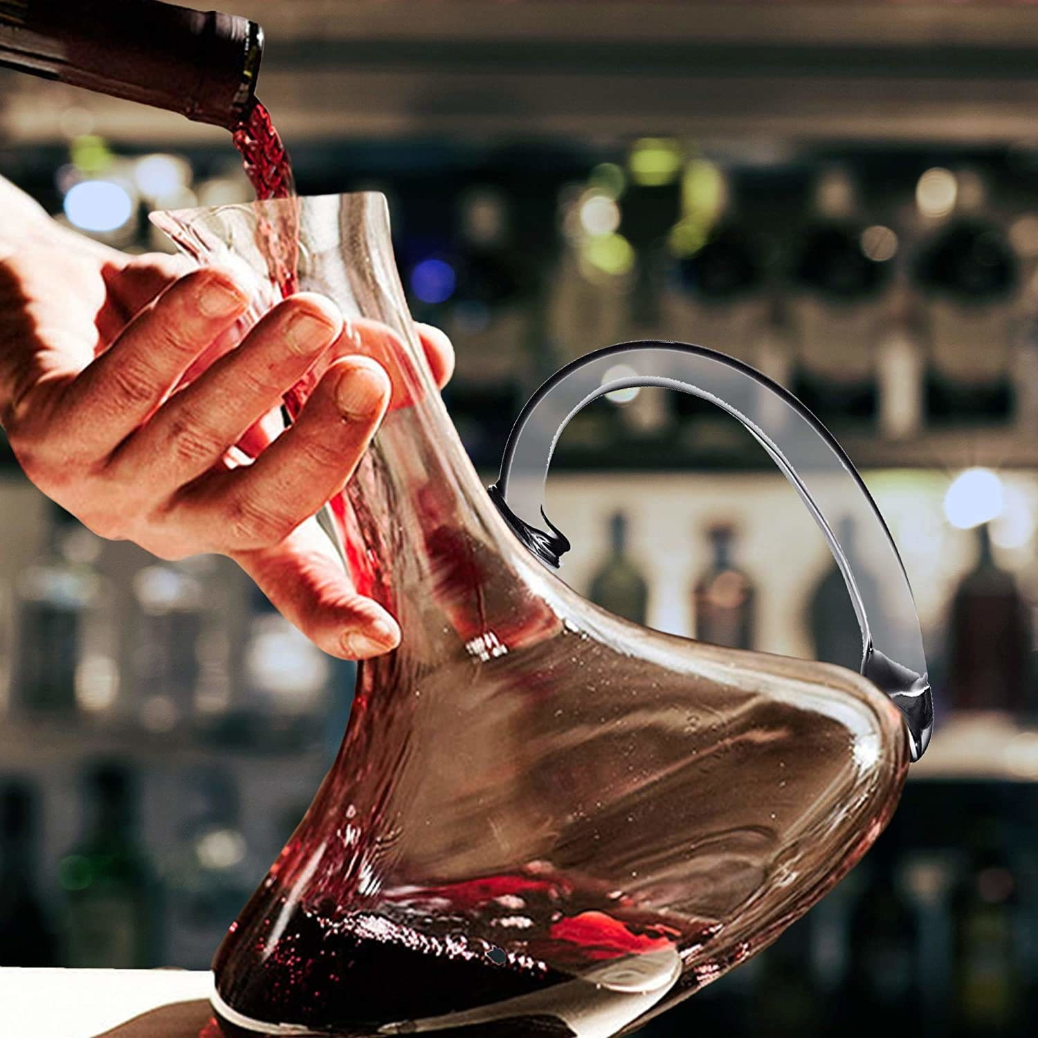 A person pouring a drink in the decanter.