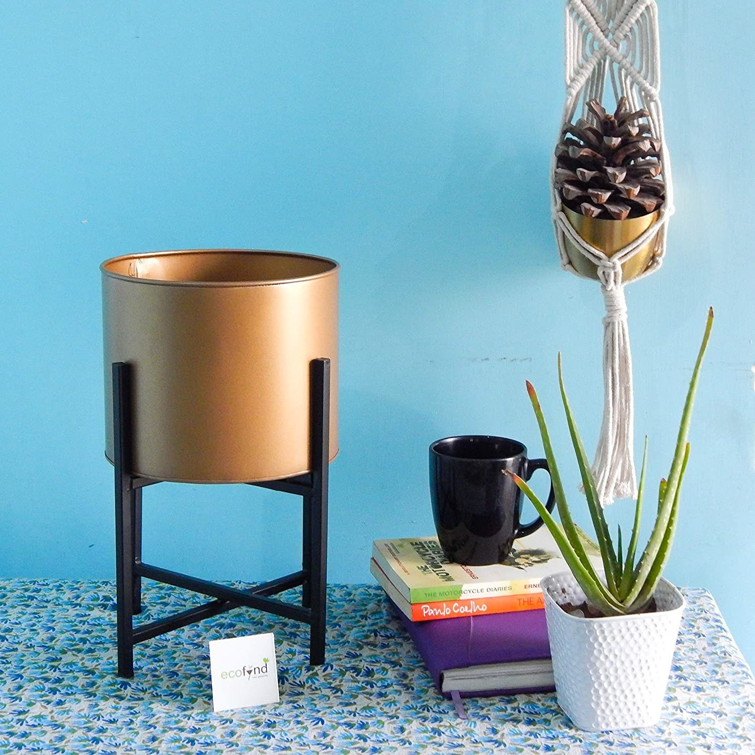 A gold cylindrical planter with a black stand.