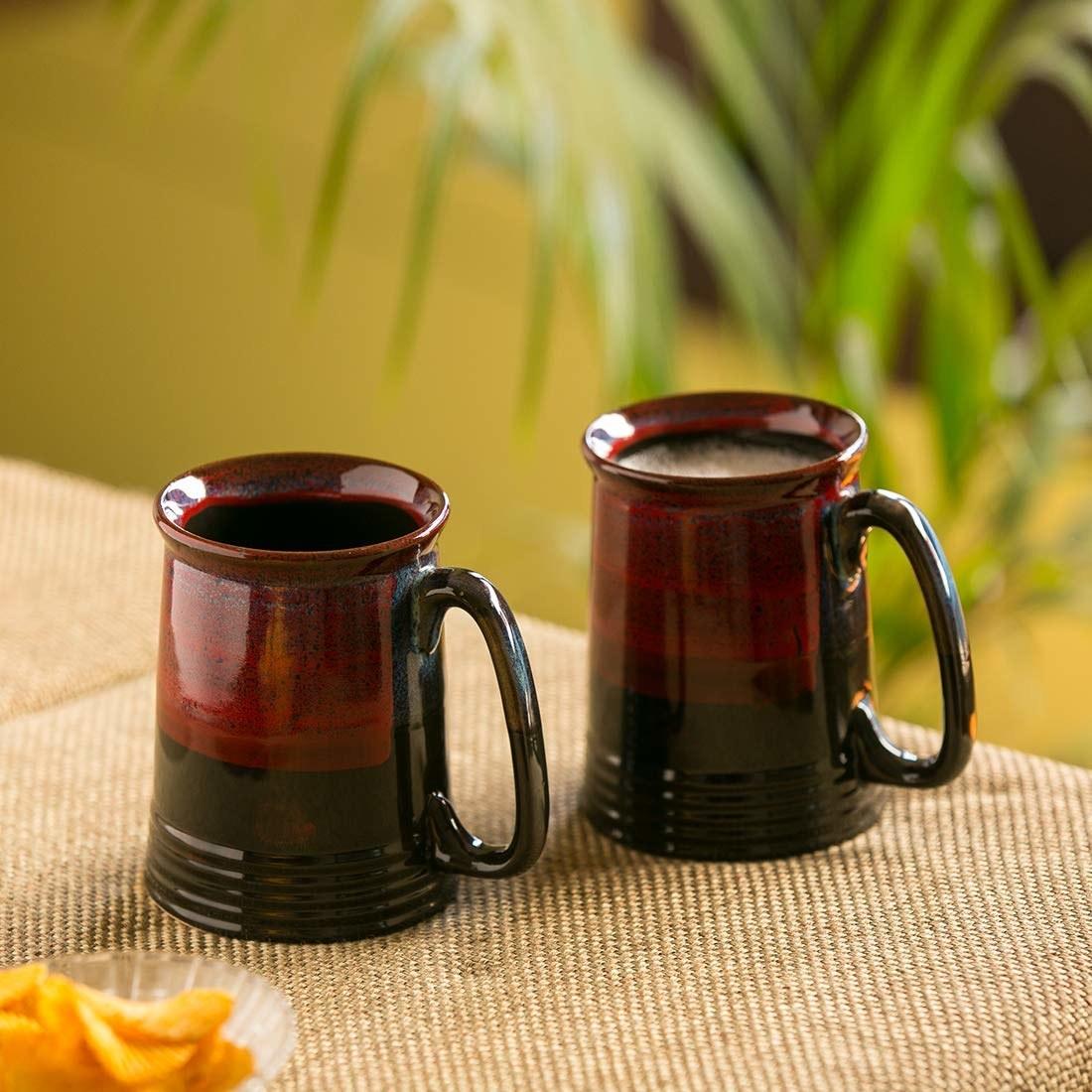 A pair of red ceramic beer mugs.