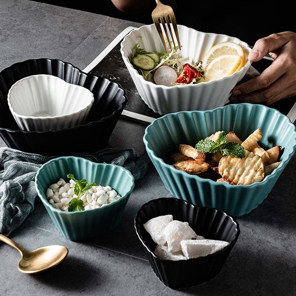 6 different coloured heart shaped bowls containing different snacks in them.