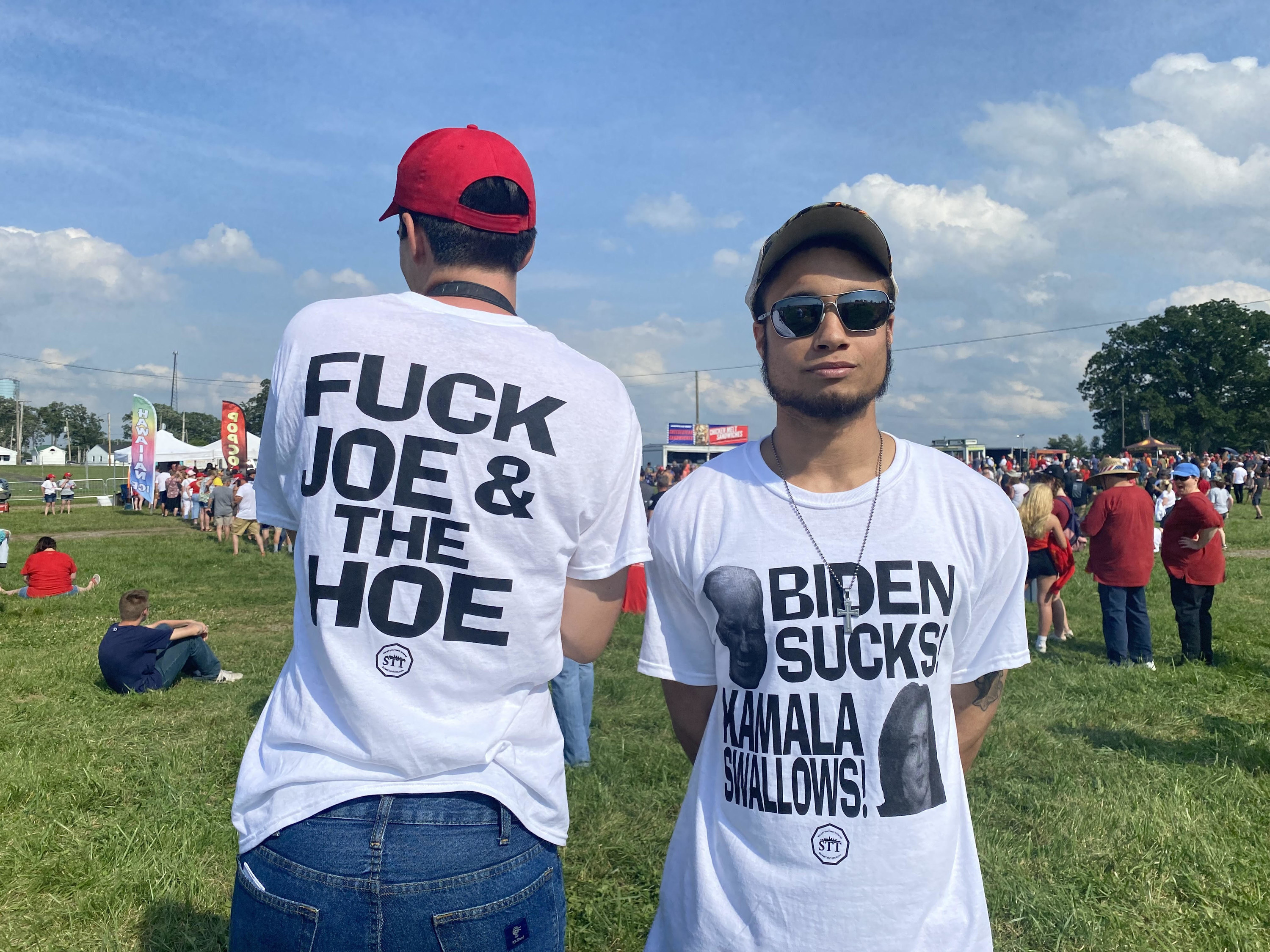 """Two people wearing the same T-shirt show """"Biden Sucks Kamala Swallows!"""" on the front and """"Fuck Joe & the Hoe"""" on the back"""