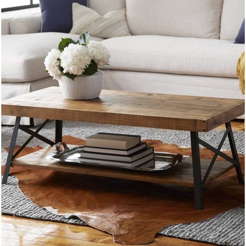 the coffee table with books on the bottom shelf and a flower vase on the tabletop