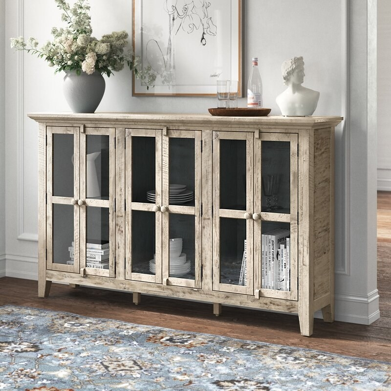 the beige sideboard with flowers and other decor on top