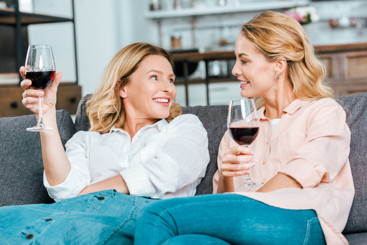 Two women sitting on a couch and sipping red wine