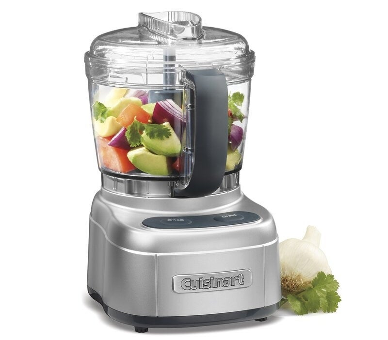 the food processor with vegetable in the basket and a garlic clove next to it