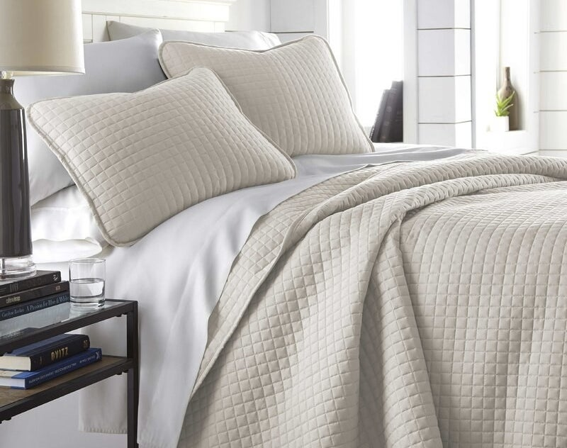 the quilt set in cream on a bed