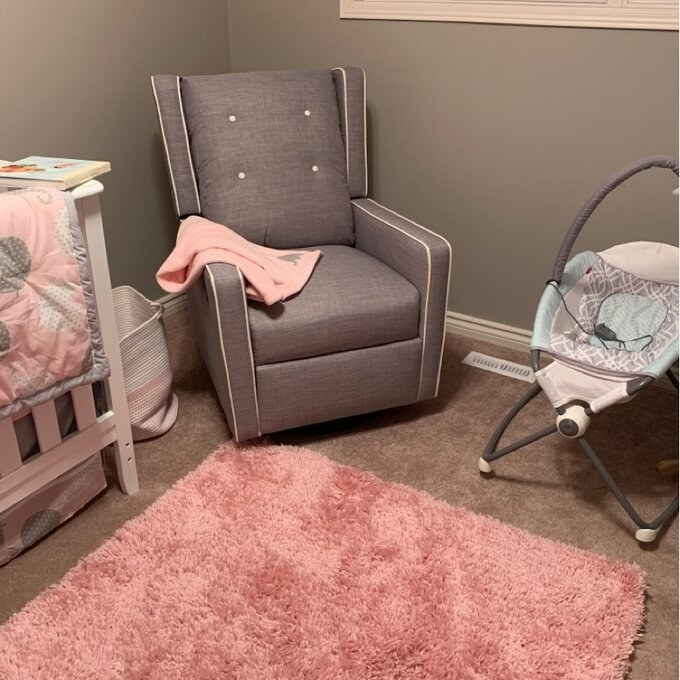 reviewer photo of the gray glider in a pink nursery with a pink blanket on it