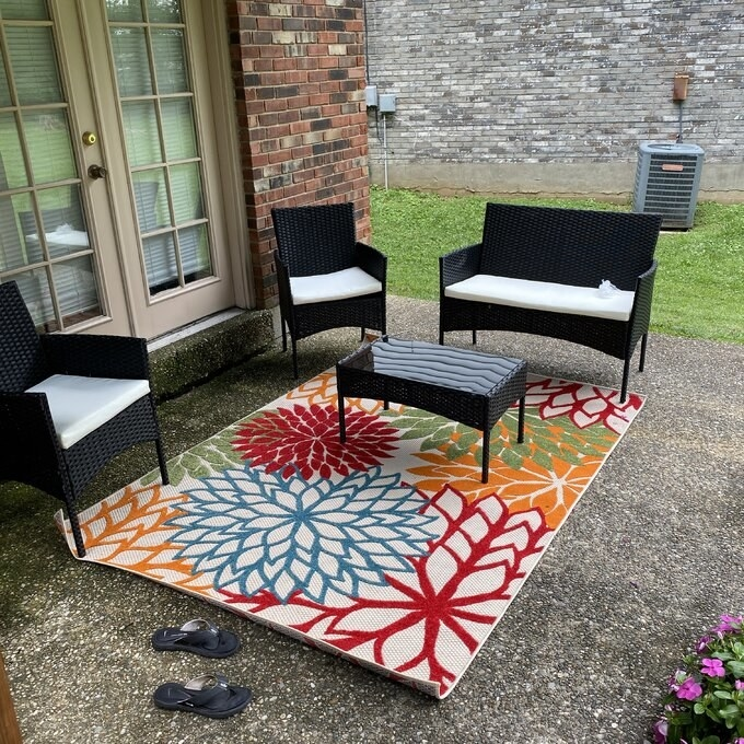 the red, blue, green, and yellow rug outside on a patio chair