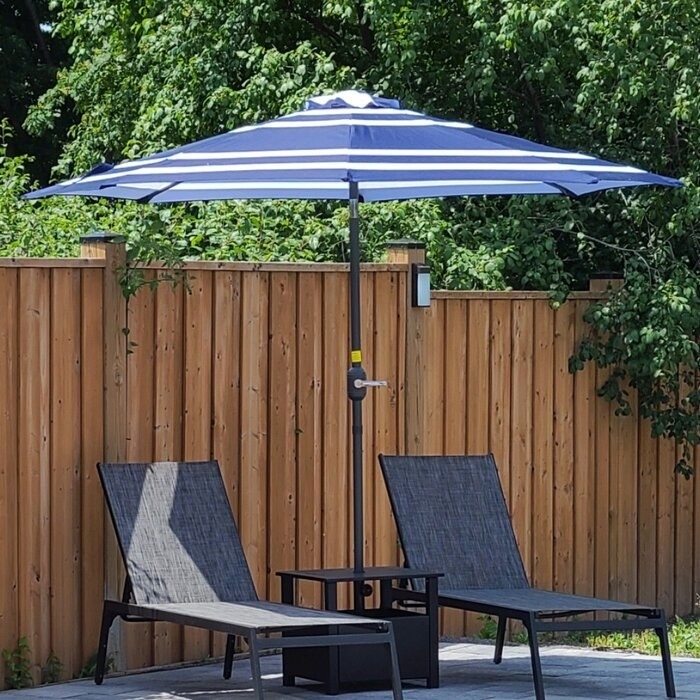 reviewer photo of the blue and white striped umbrella over two lounge chairs