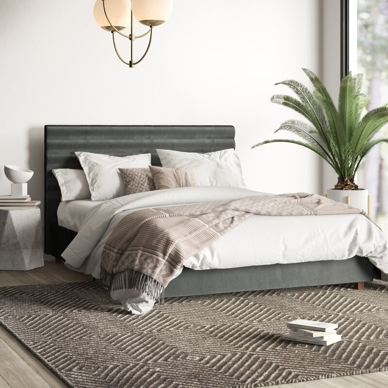 the grey bed with white sheets on top