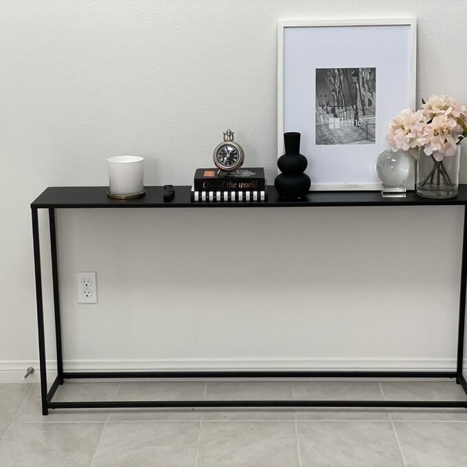 reviewer photo of the console table with books, flowers, and a framed photograph on it