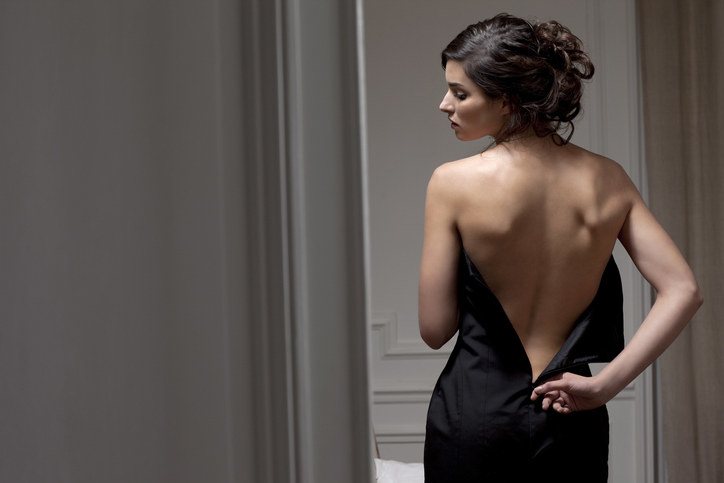 A woman unzipping the back of her dress