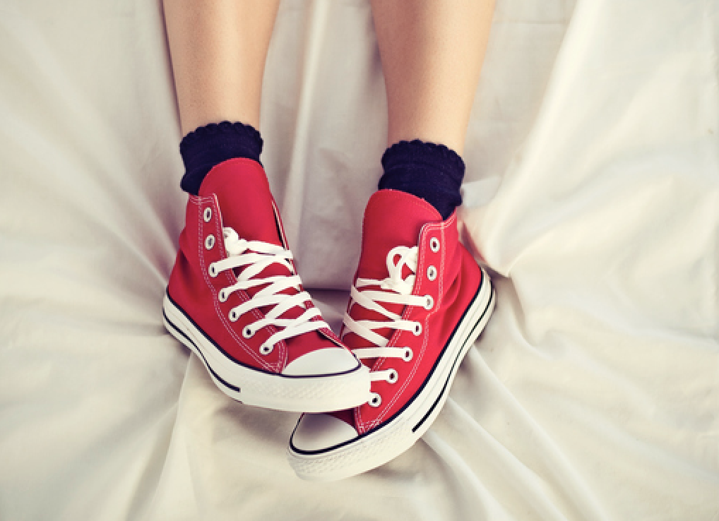 Someone wearing sneakers in bed