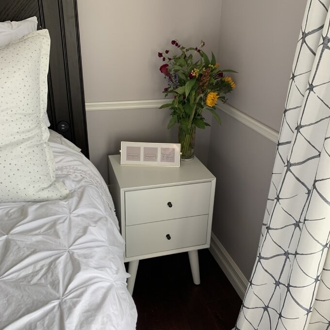 reviewer photo of the white nightstand next to a bed with flowers on top