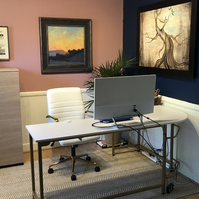 reviewer photo of the white desk with a monitor on top and desk chair behind it