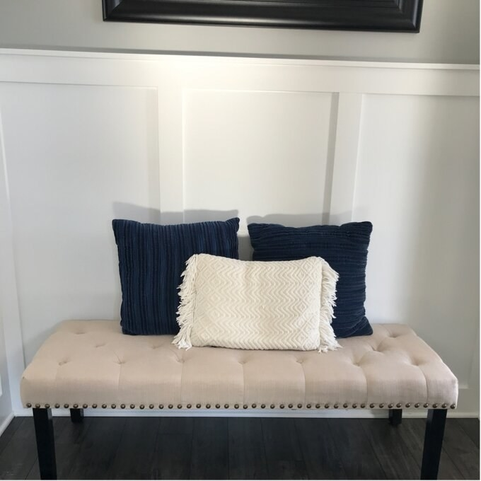 reviewer photo of the tan bench with two navy pillows and one white one