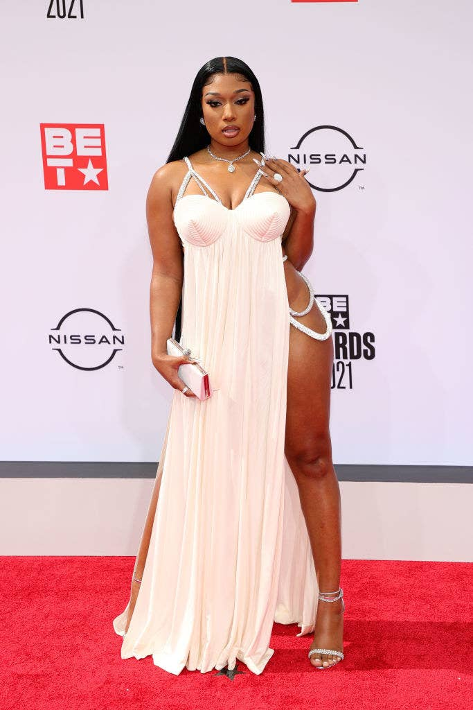 Megan Thee Stallion attends the BET Awards 2021 in a spaghetti strap dress with a thigh-high cut