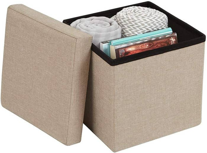 A beige stool with a lid with storage space inside.