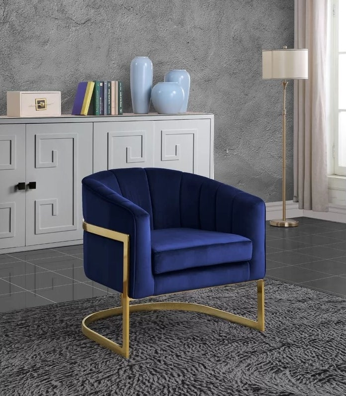 The navy barrel chair with textured velvet back and gold frame in a living room