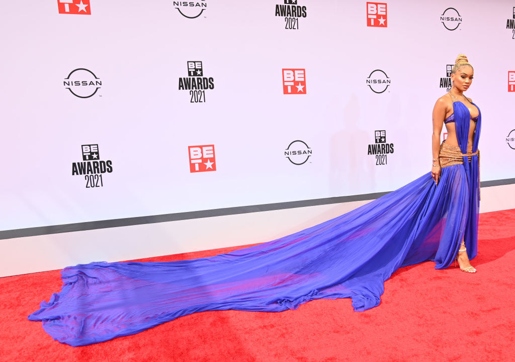 Saweetie attends the BET Awards 2021 in a low-cut gown with long flowing tail