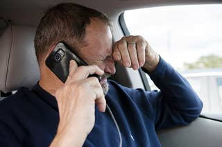 A man cries on the phone in a car after sharing some bad news, holds his hand to his head