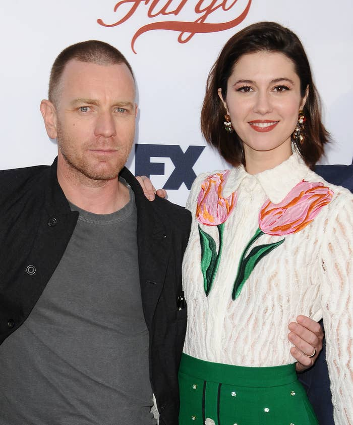 Ewan McGregor, in a black button-down and gray t-shirt, with his arm around Mary Elizabeth Winstead, in a white collared blouse with tulip patterns