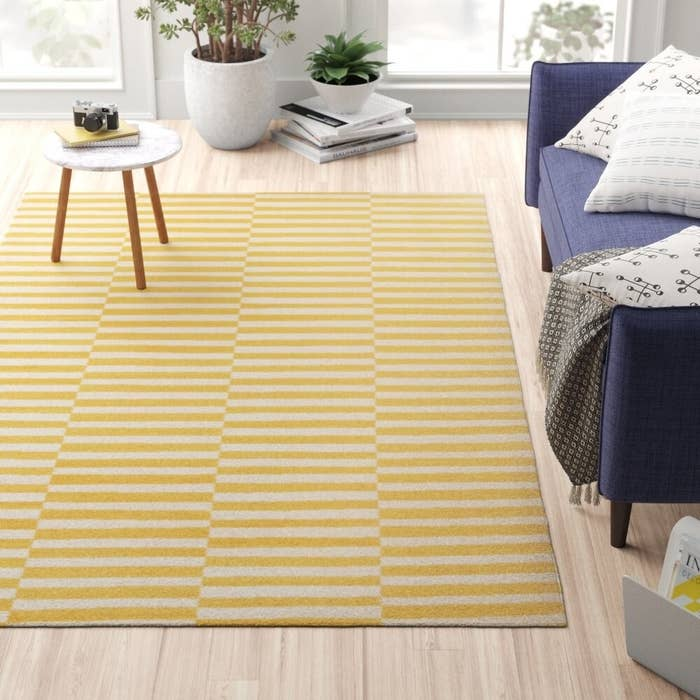 the striped rug in yellow on a living room floor