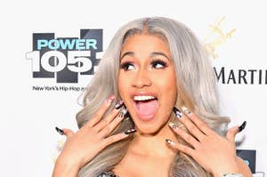 Cardi B puts her hands near her face while wearing a silver dress and long silver hair