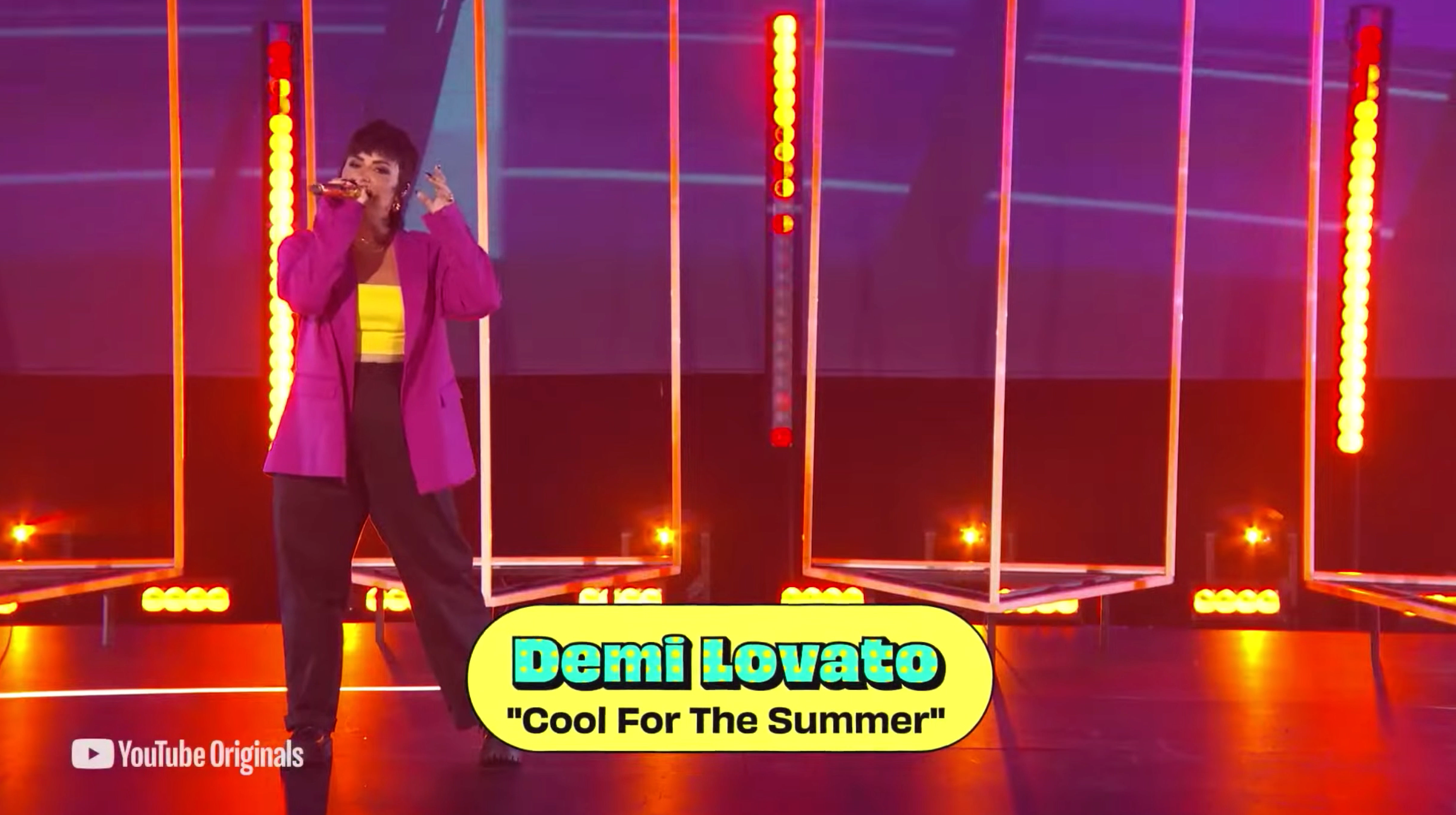 """Lovato performs """"Cool for the Summer"""" while wearing black pants, a yellor top, and a purple blazer"""