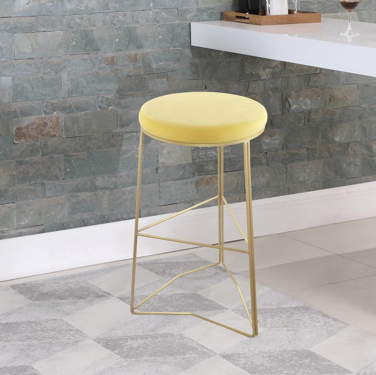 The round bar stool with a gold base and yellow cushioned seat in a kitchen