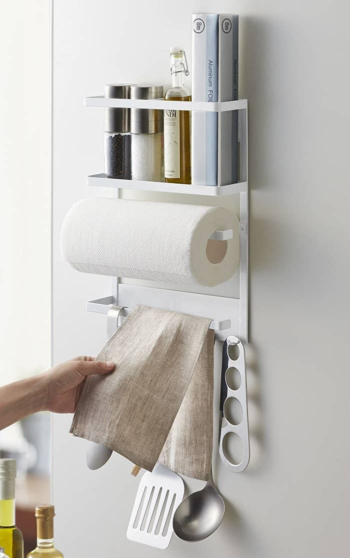 A small shelf stuck to the side of a fridge with paper towel, tea towels and scissors hanging from it
