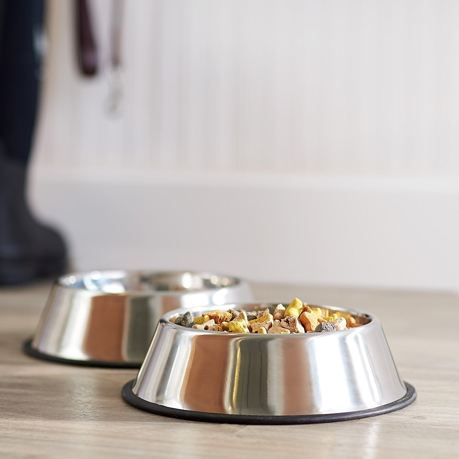 2 stainless steel bowls with food and water for pets.