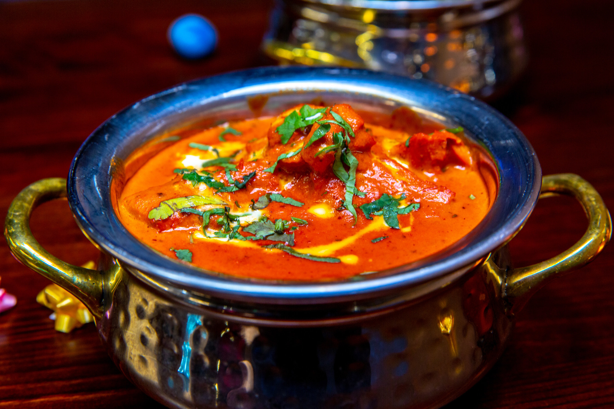 A bowl of creamy butter chicken garnished with cream, butter, and coriander