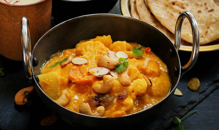 A bowl of creamy navratan korma, garnished with almonds and coriander and served with parathas