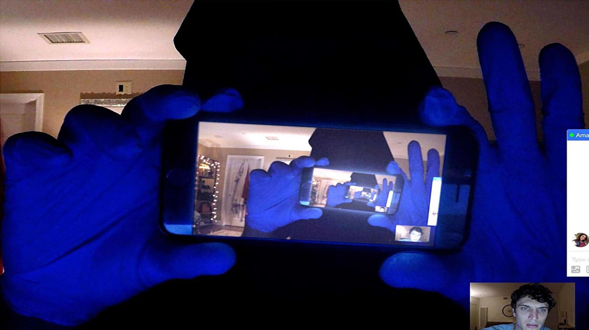a guy holding a camera phone in front of a screen and doubling the image over and over