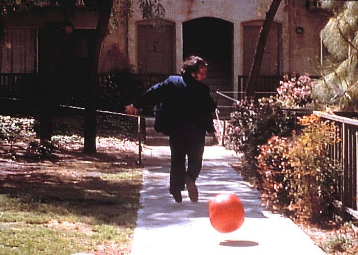 a man running away from a rolling killer tomato