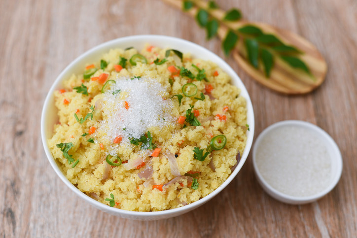 A bowl of vegetable upma, a savoury semolina based dish, that is sometimes topped with a little bit of sugar to bring out the flavours
