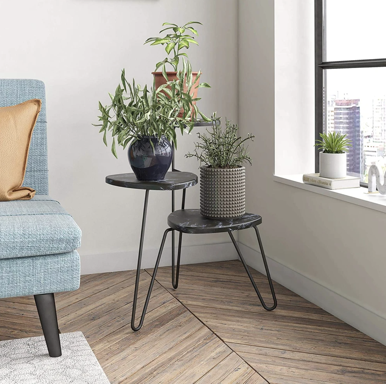 The black marble and metal plant stand displays three plants