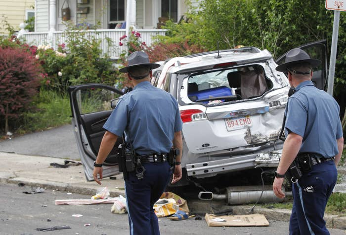 State troops are shown walking next to a battered SUV at the scene of the crime