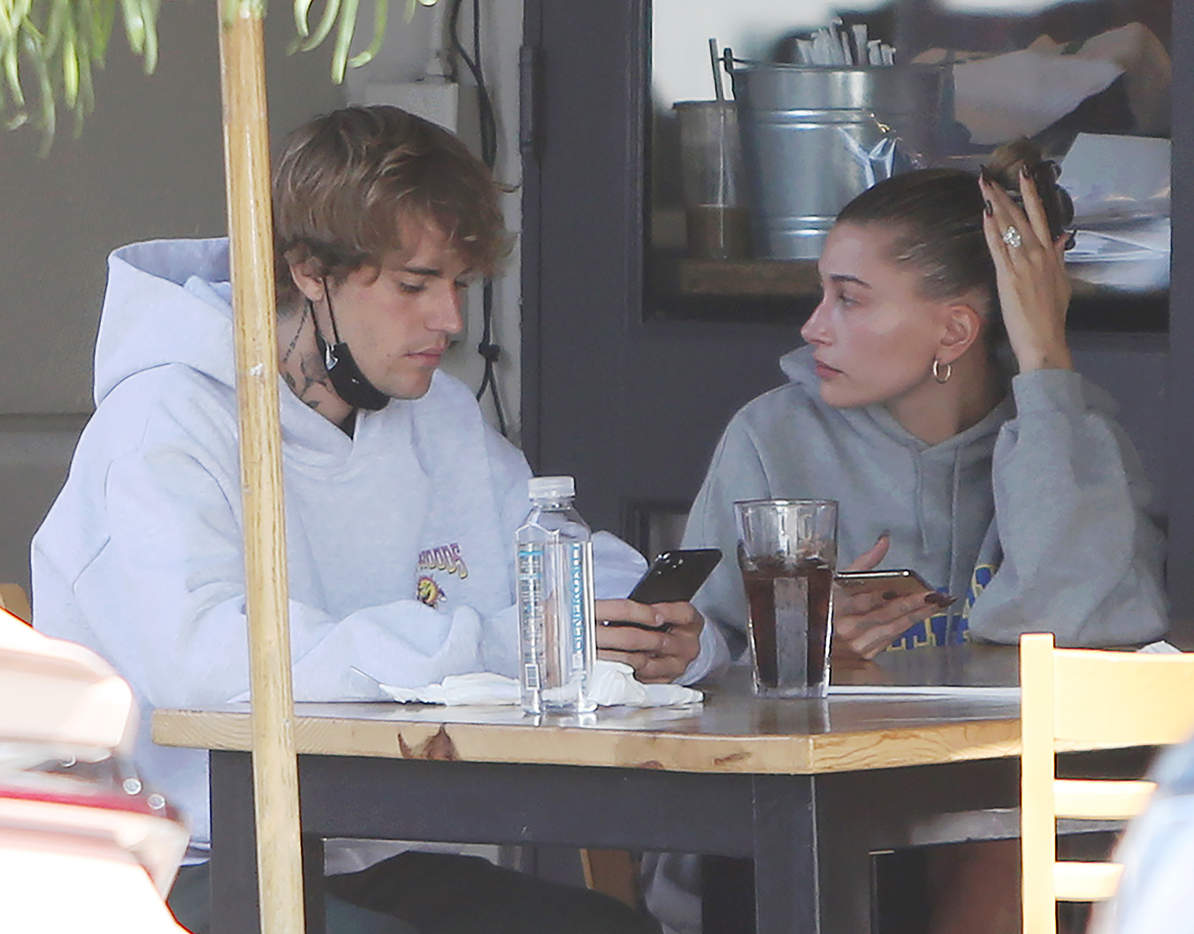 Justin sitting with his wife, Hailey Bieber, at a restaurant outdoors