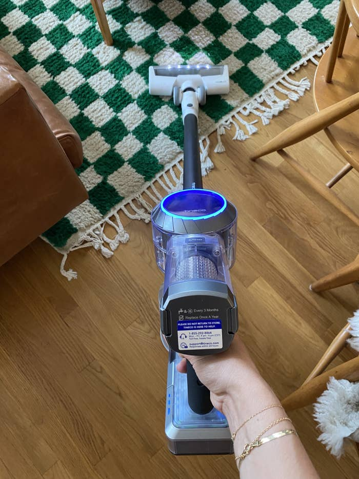 the vacuum being used on a checkered green and white rug