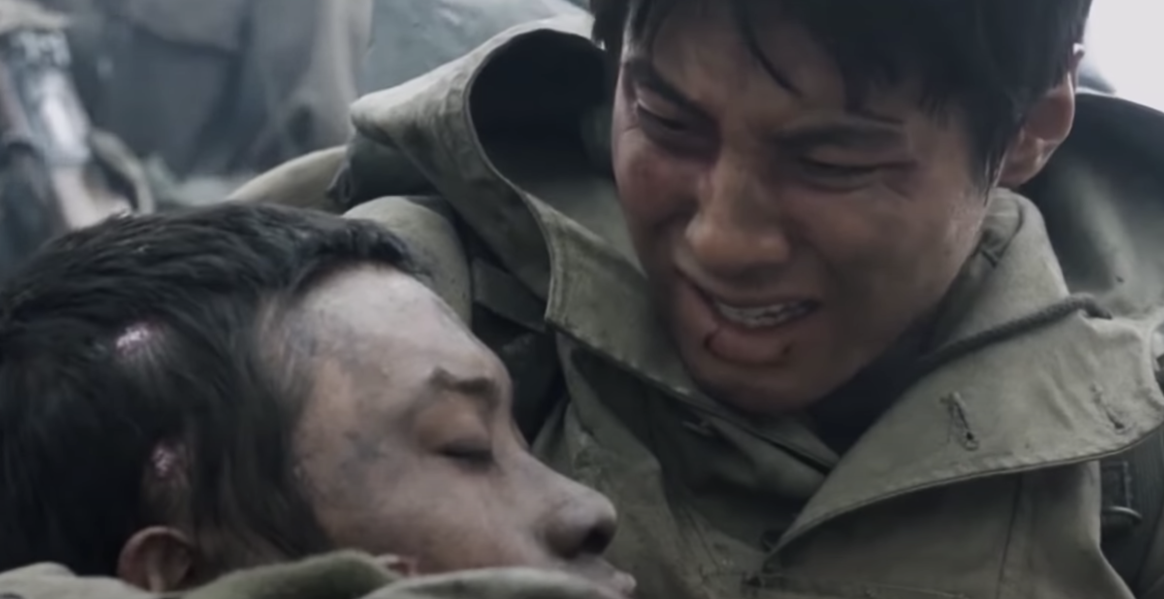 A soldier holding a fellow fallen soldier in his lap