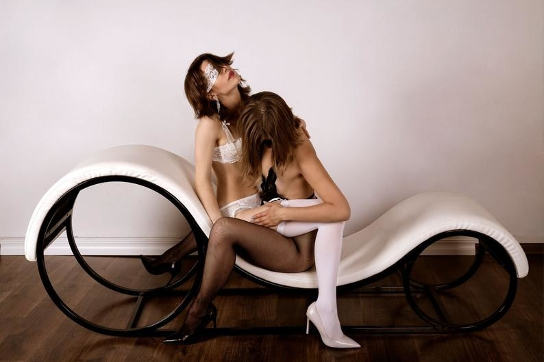 Two models sitting on white and black chaise lounge