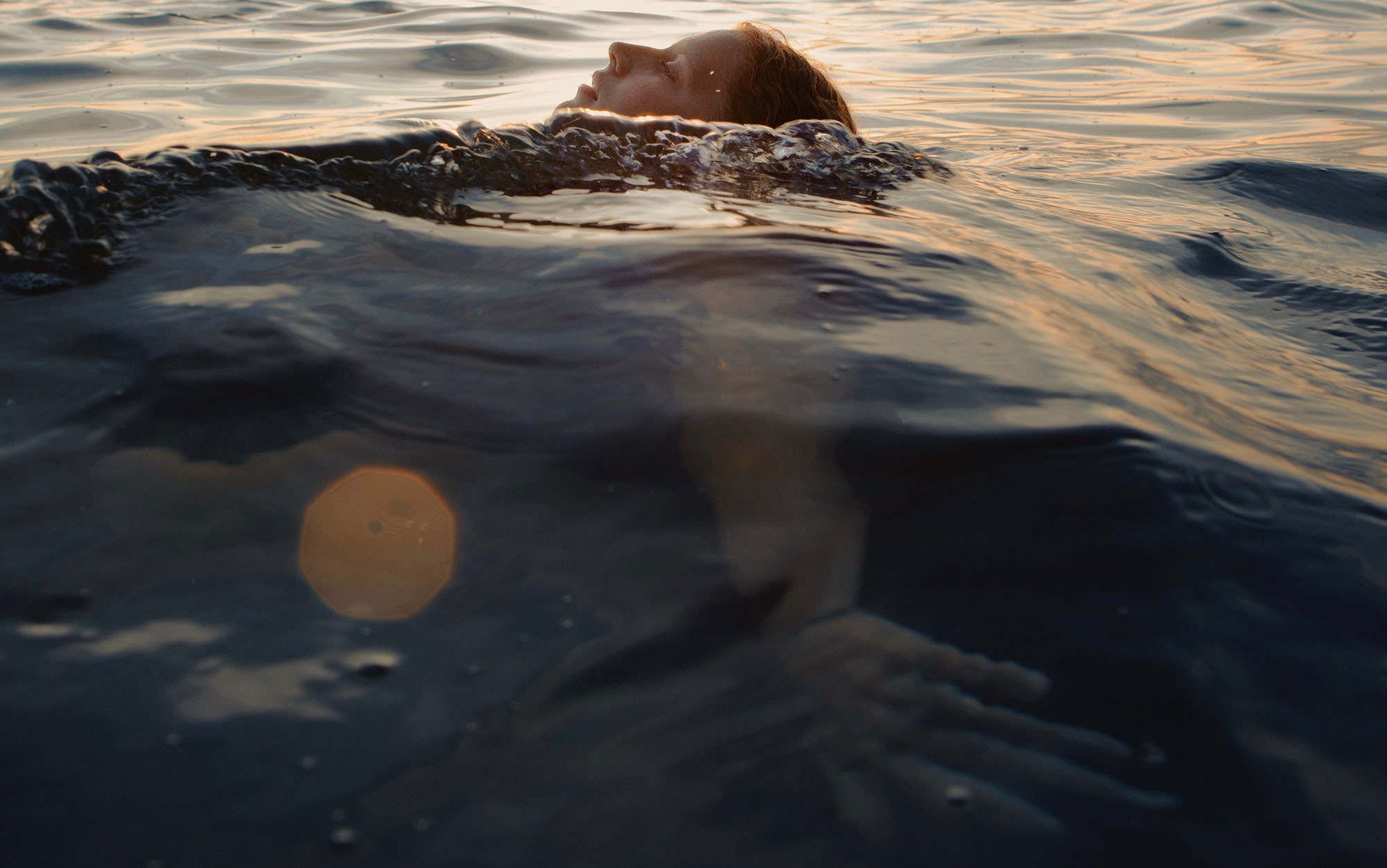 A girl floats on her back in a lake