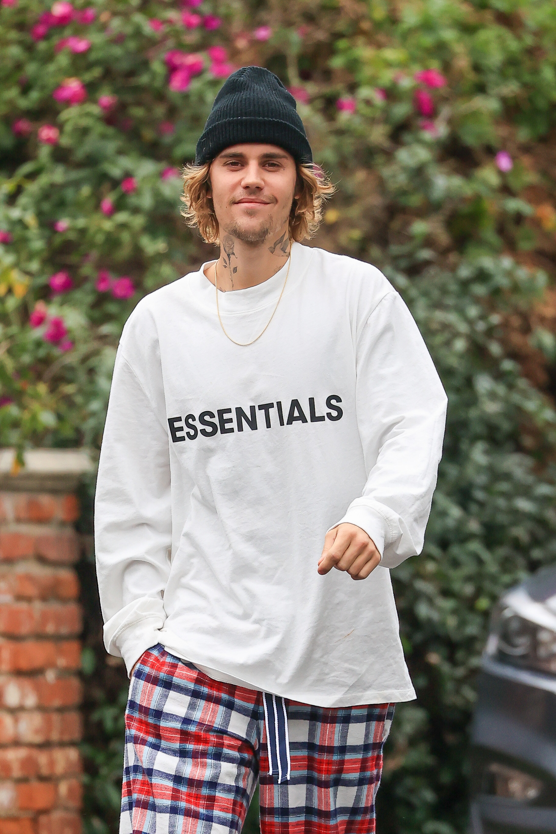 A smiling Justin outside wearing an Essentials shirt, a hat, and checkered pants
