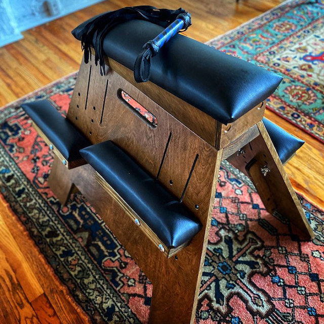 Wood stool with black faux leather cushions